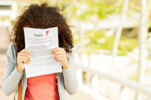 Disappointed Girl Holding Result In Front Of Face On Campus